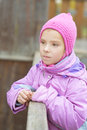 Little sad girl in pink coat around wooden railing Royalty Free Stock Image