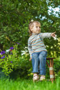 Little sad girl sitting on bench in flowered park Stock Images