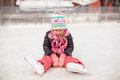 Little sad girl sitting on a skating rink after the fall this image has attached release Stock Image