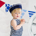 Little sailor fashion portrait of a cute boy in the striped vest and hat holding wooden steer wheel Royalty Free Stock Image