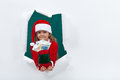 Little santa giving you money for the holiday season leaning through hole in blank board Stock Photo