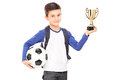 Little schoolboy holding football and a trophy isolated on white background Royalty Free Stock Image