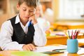 Little schoolboy sitting behind school desk during lesson in school Stock Photos