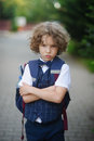 Little schoolboy stands in the school yard with an angry expression on his face . Royalty Free Stock Photo