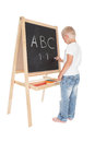 Little schoolboy writing on a blackboard over white Royalty Free Stock Image