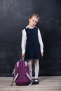 Little schoolgirl with backpack near blackboard latecomers Royalty Free Stock Photos