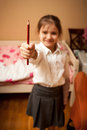 Little schoolgirl holding red pencil portrait at home of Stock Image