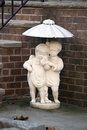 Little sculpture of children under umbrella Stock Images