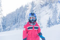 Little seven years old skier in red suit blue helmet and goggles Royalty Free Stock Photo