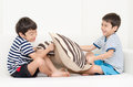 Little sibling boy playing pillow fighting on sofa in the house Royalty Free Stock Image