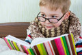 Little sick boy reading book in bed glasses Royalty Free Stock Photos