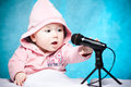 Little singer cute baby tries to sing with microphone Stock Image