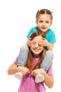 Little sister sitting on elder sister s shoulders one girl her and close her eyes with palms Royalty Free Stock Photo