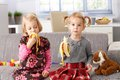 Little sisters eating banana at home sitting on sofa Royalty Free Stock Photos
