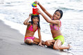 Little sisters playing two on the beach with beach toys Stock Image
