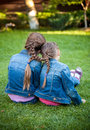 Little sisters sitting on grass head to head with joint braids two Stock Image