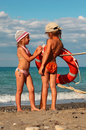Little sisters in swimsuits standing on beach Royalty Free Stock Images