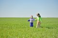 Little sisters walking in a field two the Royalty Free Stock Images