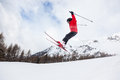 Little skier jumping in the snow male kid performs a high jump with ski winter season red jacket valle d aosta italy europe Stock Image