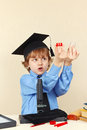 Little smart boy in academic hat conducts research with microscope Royalty Free Stock Photo