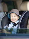 A little smiling asian boy in the car seat Stock Photography