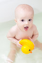 Little smiling baby with duck sitting bathtub Stock Image