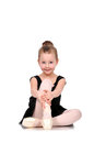 Little smiling ballerina in pointe sitting on floor Royalty Free Stock Photos
