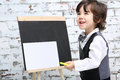 Little smiling boy in bow tie stands next to chalk board with sheet studio Royalty Free Stock Photos
