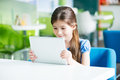 Little smiling girl with apple ipad air kiev ukraine may sitting at the desk and looking on a brand new developed by Royalty Free Stock Image