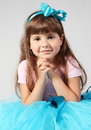 Little smiling girl hands together portrait sitting studio shot Royalty Free Stock Photo