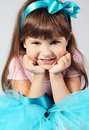Little smiling girl hands under chin portrait sitting proping up Stock Images