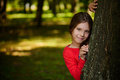 Little smiling girl is hiding behind tree Royalty Free Stock Photo