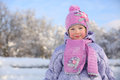 Little smiling girl in pink scarf and hat stands near trees snow at winter day Royalty Free Stock Photography
