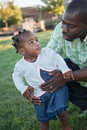 Little smiling girl playing with dad african american outdoor Stock Photo