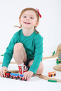Little smiling girl plays with train and wooden railway on white background Royalty Free Stock Image
