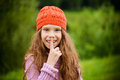 Little smiling girl puts finger to his mouth beautiful in a red cap a Stock Photos