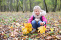 Little smiling girl squats and holds maple leaflets yellow in autumn forest shallow depth of field Stock Image