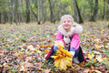 Little smiling girl squats with maple leaflets yellow and looks at camera in autumn forest shallow depth of field Royalty Free Stock Image