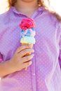Little smilling girl holding ice cream cone in her hands outdoors Royalty Free Stock Photo