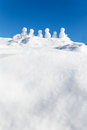 Little snowmen figures standing on a mountaintop, copyspace in t Royalty Free Stock Photo