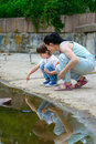 Little son showing something in the water to his mother Stock Photography