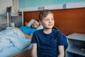 Little son sitting on chair near his sick father sleeping on hospital bed at ward Royalty Free Stock Photo