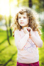 Little sunny girl is smiling in autumn park. Royalty Free Stock Photo