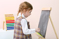Little surprised girl draws by chalk on chalkboard near colorful abacus in studio Stock Image