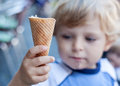 Little toddler boy eating ice cream in cone summer selective focus on Royalty Free Stock Photography