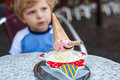 Little toddler boy eating ice cream in summer city cafe selective focus on Royalty Free Stock Photo