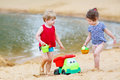 Little toddler boy and girl playing together with sand toys