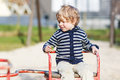 Little toddler boy having fun on old carousel on outdoor playgro playground Stock Image