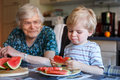 Little toddler boy and his great grandmother eating watermelon a in home kitchen selective focus on child Royalty Free Stock Image