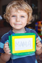 Little toddler boy with painting board writes his first word mama Stock Images